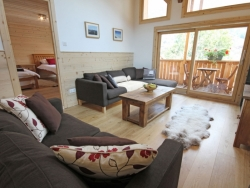 The spacious lounge of Chalet Jouet with a splendid log fire