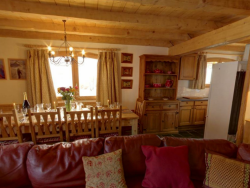 The spacious lounge of Chalet La Forge with a splendid log fire