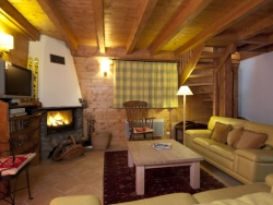 The living area of The Great Escape chalet with a roaring log fire