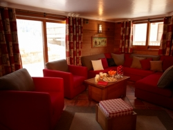 The spacious lounge of Chalet Renardeaux with a charming log fire