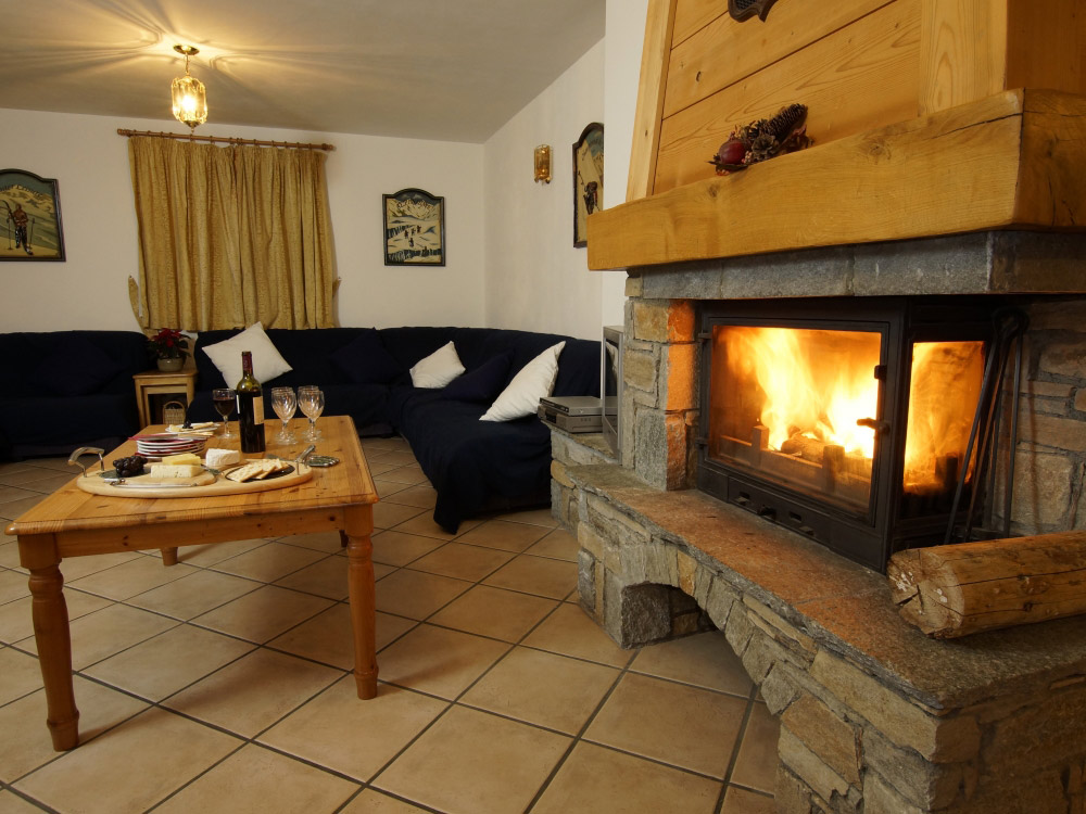 The spacious lounge of Chalet Anniek with a roaring log fire
