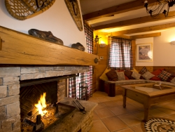 The spacious lounge of Chalet Lea with a warming log fire