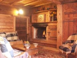 The living room of Chalet Laiterie with a wonderful log fire