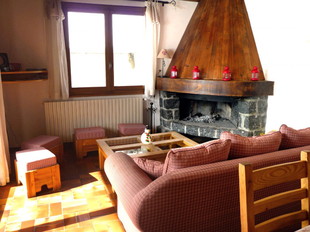 The spacious lounge of Chalet Chez Claude with a warming log fire