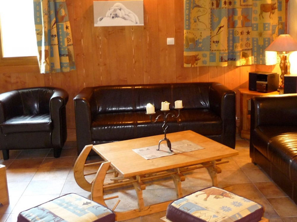 The living area of Chalet Chery des Meuniers with a charming log fire