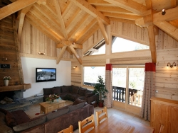 The spacious lounge of Chalet Starski with a roaring log fire