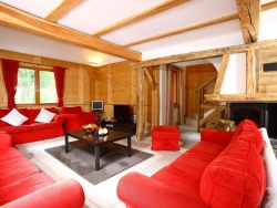 The living area of Chalet Ancolies Lodge with a wonderful log fire