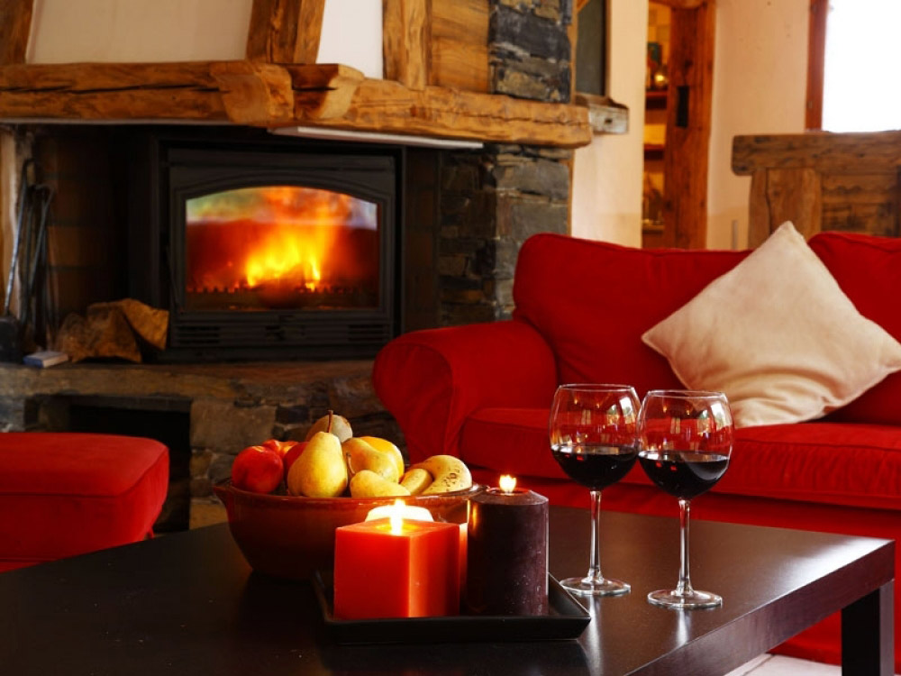 The spacious lounge of Chalet Ancolies Lodge with a warming log fire