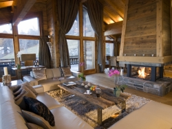 The living room of Chalet Ighzer with a roaring log fire