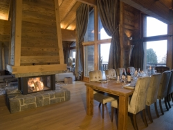 The spacious lounge of Chalet Ighzer with a charming log fire